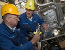 Zwei BASF-Mitarbeiter überprüfen an einer Amine-Produktionsanlage einen Sensor an einer Pumpe