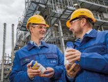 Dr. Stefan Gräter und Dr. Andreas Kicherer zeigen eine Probe von Pyrolyseöl und damit hergestellten Kunststoff vor dem Steamcracker